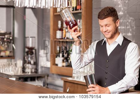 Attractive male bartender is making alcohol drink
