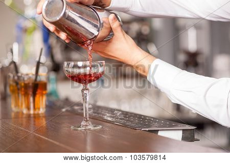 Professional male bartender is preparing drink in pub
