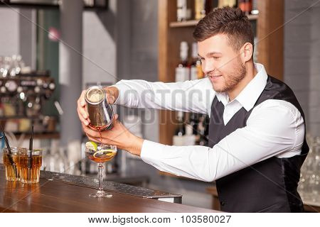 Cheerful young barman is making cocktail in bar