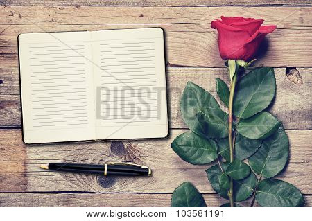 Vintage Rose And Diary On Wooden Background