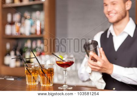 Attractive male bartender is shaking drink in pub