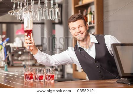 Attractive male barman is making cocktails in bar