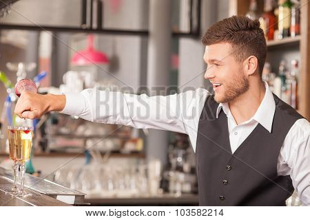 Handsome male barman is creating alcohol drinks