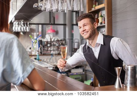 Cheerful young barman is working in bar