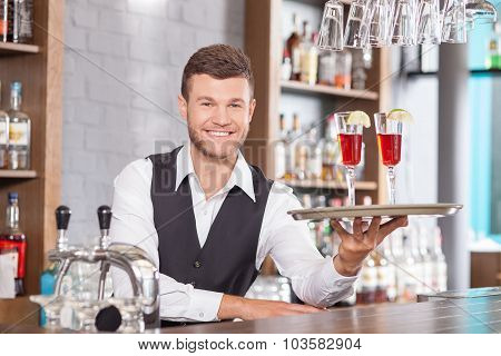 Attractive young barman is serving customers in bar