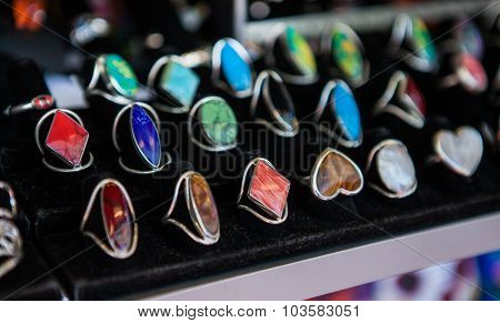 Closeup of hand made rings with colorful stones on market