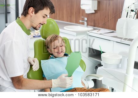 Attractive dental doctor is treating small patient