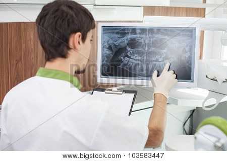 Cheerful male dental doctor is working in lab