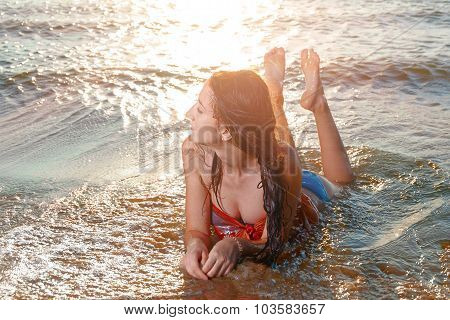 Young beautiful woman lying on the beach sunbathing