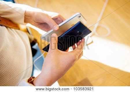 Woman comparing the new iPhone 6s with Microsoft Lumia