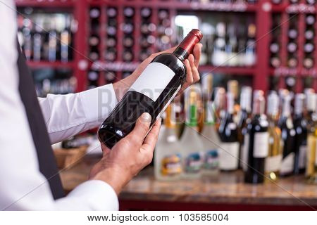Professional young sommelier is carrying alcohol drink