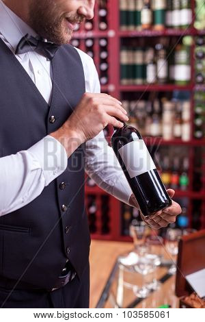 Cheerful young male waiter is working in liquor store