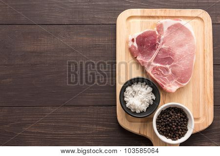 Top View Raw Pork Chop Steak And Salt, Pepper On Wooden Background