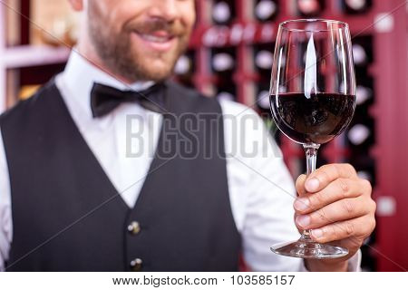 Cheerful young male waiter is carrying wineglass