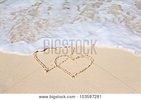 Two Hearts Drawn On The Beach Sand, The Waives Wiping The Hearts Out