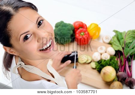 Close up portrait of indian woman looking over her shoulder while cooking and preparing food in the kitchen