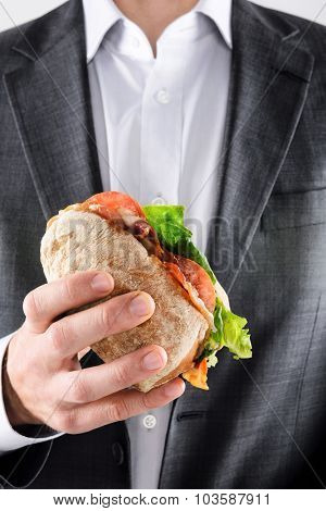 Business man in suit holding his lunch ciabatta sandwich roll with bacon lettuce and tomato