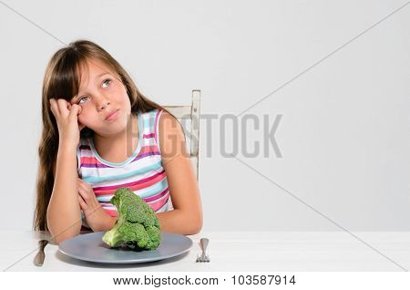 Cute young girl is bored with her food, looking up and uninterested in vegetables and healthy produce