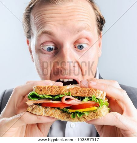 Funny humourous man eating a sandwich with exagerated wide eye comical expression