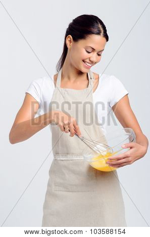 Pretty smiling woman home chef beating eggs with whisk and glass bowl for baking or food preparation