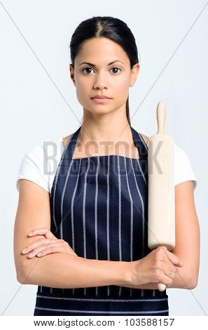Portrait of a beautiful woman baker with a serious expression, full of focus and determination, holding a rolling pin