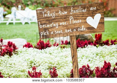 wooden sign with white writing and a white heart