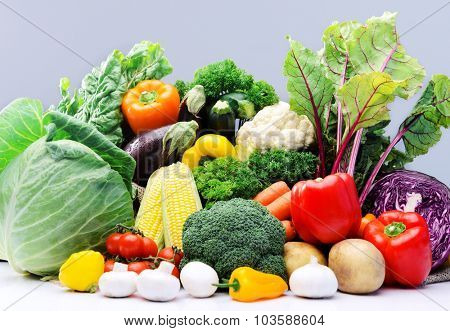 Raw fresh vegetables from the farmers market, broccoli, cabbage, beetroot, mushroom, tomato, garlic, squash, sweetcorn isolated on light grey background