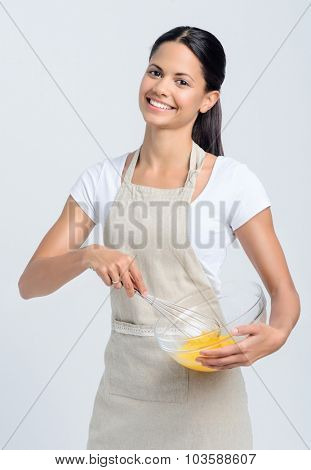Happy pretty chef beating eggs in a glass bowl