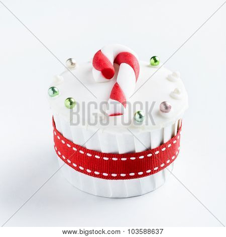 Christmas cupcake in traditional red green colours with candy cane decorative element