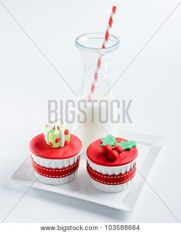 Red festive christmas cupcake with mistletoe and gift box decoration with mini jug of milk