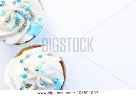 Cupcakes with frosting and decorations on white background
