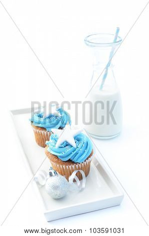 Festive holiday cool tone blue winter cupcakes with large star, christmas decorations and milk bottle