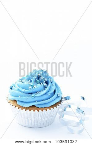 Vanilla cupcake with blue buttercream icing and decorative silver balls and ribbon