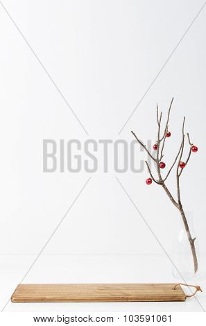 Christmas table decoration in simple, minimalist, elegant style with bare branch and red baubles, plenty of copy space