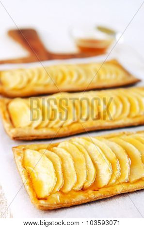 Delicious looking layered apple pastries served on a rustic wooden platter