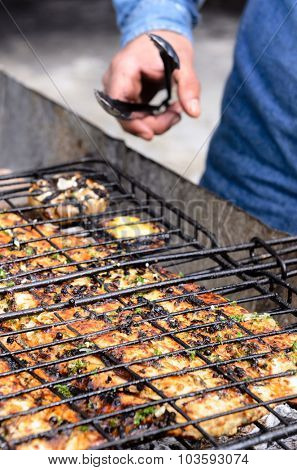 Hands with grilled fish at a barbecue barbeque bbq, in the cooking process