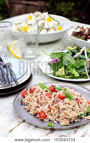 Garden summer entertaining, buffet style with different salads on the table, green leafy, brown rice pilaf with cherry tomatoes