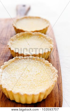 Delicious lemon tart confectionery served on a wooden platter