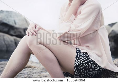 Unknown woman in a pink chiffon blouse posing by the seaside