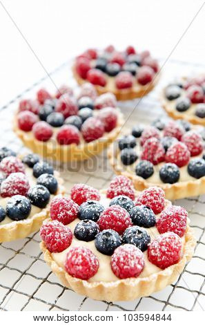 Cooling tray of raspberry and blueberry tarts sprinkled with icing sugar