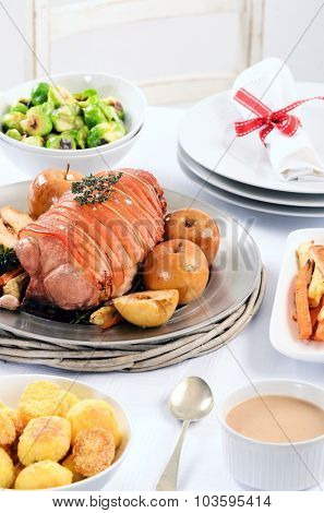 Christmas table meal with pork roast, potatoes, honey glazed carrots, brussel sprouts sides and wine on a festive table