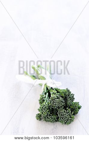 Exotic vegetable, broccolini in a bundle on rustic white background
