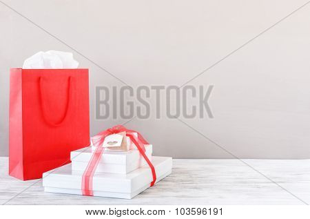 Gift boxes tied with ribbon and shopping bag on table top, christmas valentines birthday presents, plenty of copy space