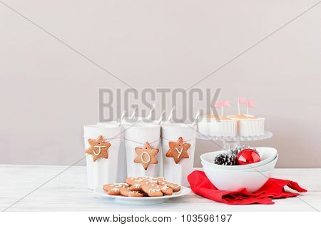Red and white christmas table decoration setting with gingerbread stars tied with bakers twine to cups as ornaments
