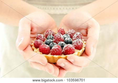 Woman in apron presenting a fruit tart, her hands forming a heart shape