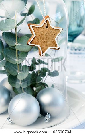 Christmas centerpiece of silver baubles, green leaves in a glass dome decorated with gingerbread star, home DIY for the festive season