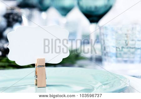 Christmas table setting in blue white and green theme with empty place card