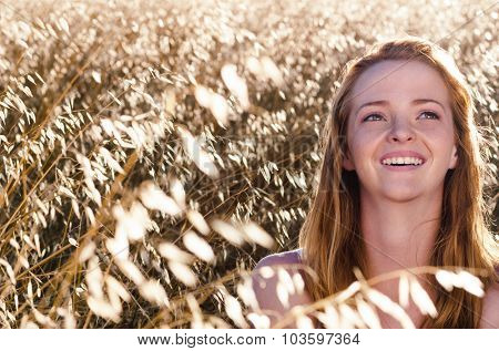 Beautiful happy carefree young woman sits in field of golden weeds and poses for a portrait