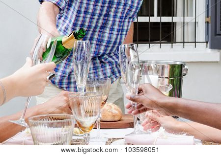 Man pours champagne into glass flutes held by hands of multi racial origins, no faces