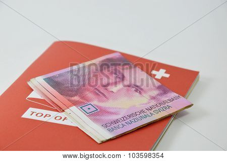 Swiss banknote and red book